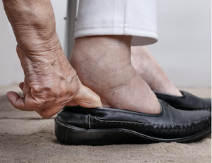 senior in assisted living trying to get shoe on